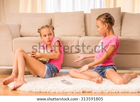 One of sisters hides a bucket of popcorn while watching tv with her twin sister. - stock photo