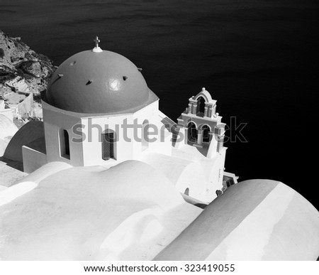 One of the famed blue church domes of Oia on the island of Santorini in the Greek Islands is highlighted against the water in the background. (Scanned from black and white film.) - stock photo
