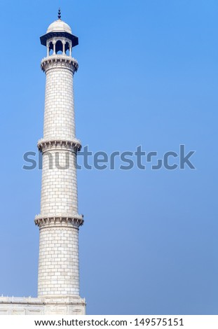 One of the four Taj Mahal minarets against blue sky in India's Agra. White marble tower isolated against blue sky.