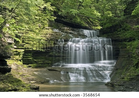One of the hundreds of gorge waterfalls found in New York's Finger Lakes region. Spring colors along the stream add to the beauty of the scene.  Just one of many waterfalls in my collection. - stock photo