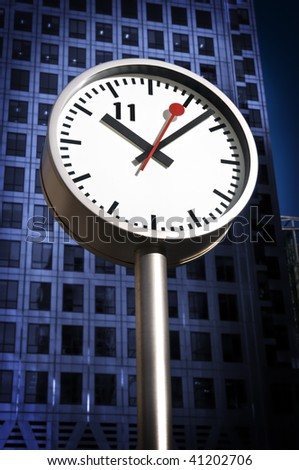 One of the iconic Clocks of Canary Wharf .Canary Wharf Tower is in the background. - stock photo