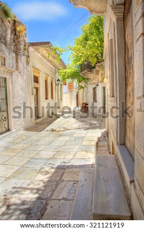 One of the many picturesque sunny cobble stone streets at the town of Naxos, Greece - stock photo