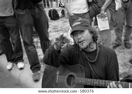 One of the many protesters sits in front of the White House playing guitar.