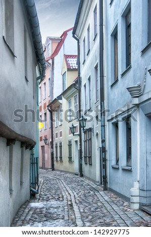 One of the many quaint little narrow streets in the old town region of Riga. - stock photo