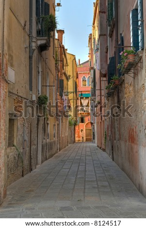 One of the many streets that are so typical for the city of Venice. - stock photo