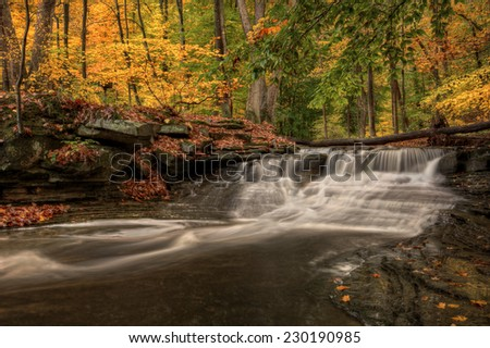 One of the many waterfalls along the Sulpher Springs Creek in Ohio. This waterfall looks it's best with peak autumn colors in the trees. Located in the South Chagrin Reservation Cleveland Metroparks. - stock photo