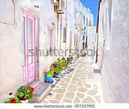 One of the many white washed picturesque sunny cobble stone streets at the Cyclades  Island of Mykonos, Greece  - stock photo