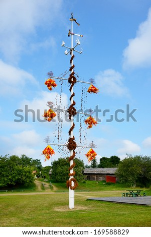One of the maypoles typical for Aland Islands; celebration of midsummer day in villages - stock photo