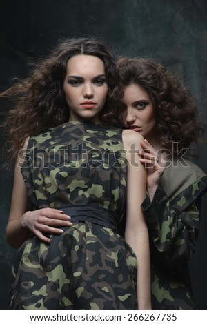 one of the parties to the conflict seek the protection of his interests . Young girls in military uniform - stock photo