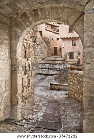 One of the pedestrian streets of the town from the Middle Ages called Albarracin, located in Spain, with an arch made of stone framing the image - stock photo
