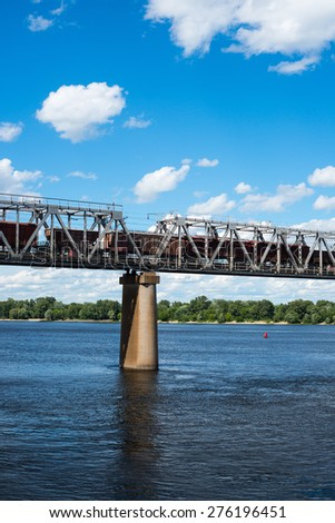 One of the piers supporting the railroad bridge across the Dnieper in Kyiv. Freight train passing across the bridge. - stock photo