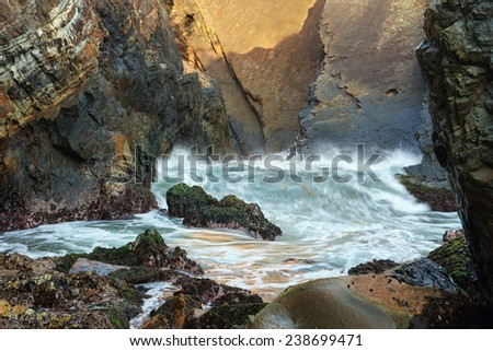 One of the smaller waves coming through the Suparloaf Point sea cave chasm.  It was  formed by weakness in the cliff eventually eroded out; and enlarged by thydraulic pressure built up by each wave. - stock photo