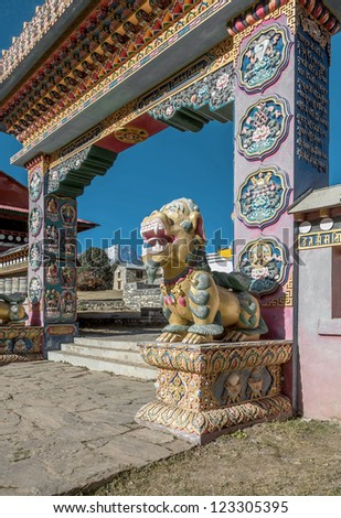 One of the two mythical beasts (right) guarding the gate of the Tengboche monastery - Nepal, Himalayas - stock photo