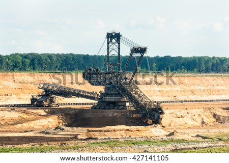 One of the world's largest bucket-wheel excavators is digging lignite (brown-coal) in of the world's deepest open-pit mines in Hambach in the Ruhr area in Germany. - stock photo