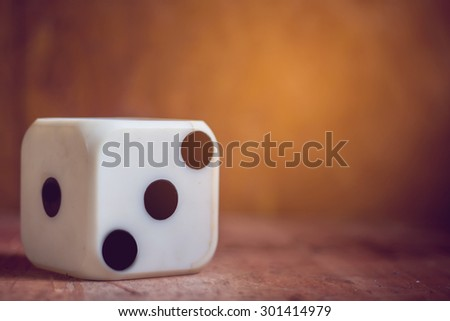 one old dice on wooden table,vintage color tone,abstract background to risk management concept.