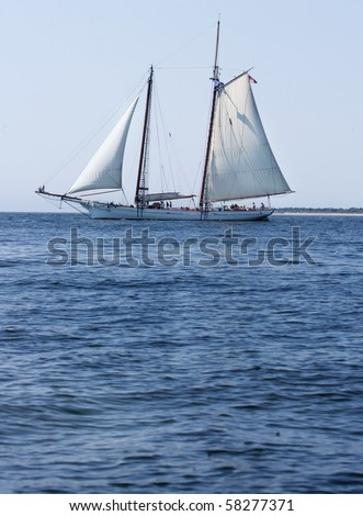 one old fashioned sailboat schooner on a blue sea clear day - stock photo