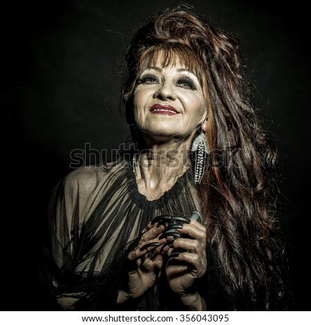 One old scary smiling witch woman with long red knotty hair in blouse with black long nails on hand as halloween character with bright makeup in studio on black background, square photo - stock photo