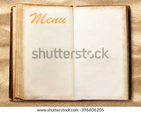 One open blank vintage menu book on sand - stock photo