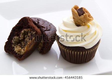 one open cupcake showing the cookie dough, one cupcake with white frosting and a cookie piece as decoration - stock photo