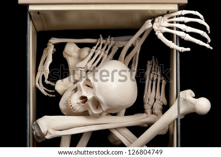 One open drawer reveals skeletal bones that were previously hidden. - stock photo