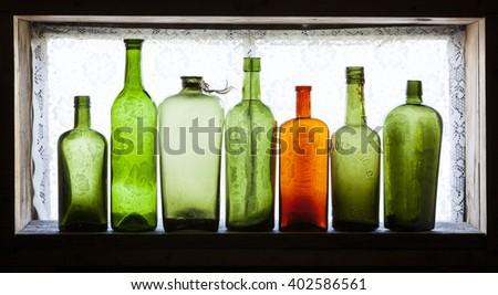 One orange bottle among green antique bottles on old windowsill in daylight. Curtain pattern visible through glass.  - stock photo