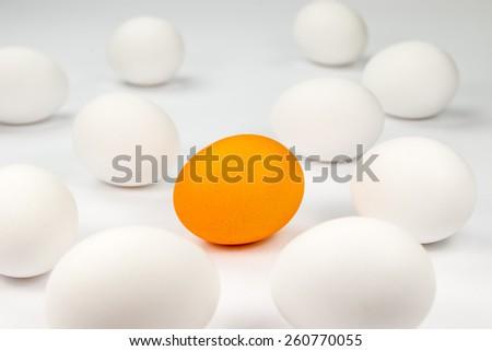 One orange egg among white eggs on a white background  - stock photo