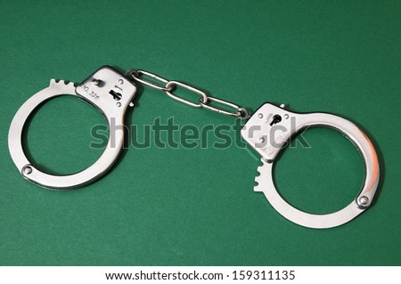 One Pair of Handcuffs on a Colored Background - stock photo