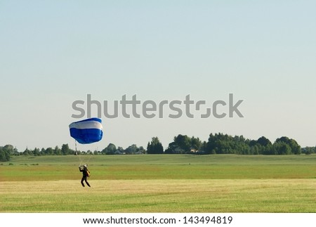 One parachute, landing parachutist, Skydiver with parachute landed, Paragliding in evening sunset sky background,sunset, Lithuania,sport, parachutist in the field,active lifestyle, mens sport - stock photo