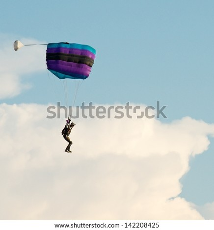 One parachute, landing parachutist, Skydiver with parachute open landing, Paragliding over the clouds against blue sky Paraglider flying in the blue sky with clouds backgrounds,sunset, Lithuania,sport - stock photo