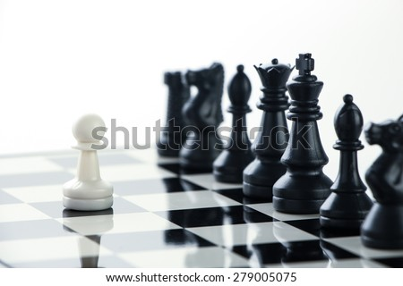 One pawn is staying against a lot of chess pieces. - stock photo
