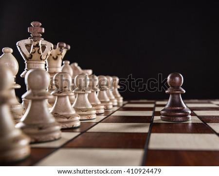 One pawn staying against full set of chess pieces, close-up. - stock photo
