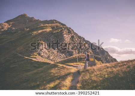 One person hiking uphill on footpath in the italian Alps with panoramic view on the mountains. Summer adventures and exploration on the Alps. Toned image, vintage filter style, vignetting added. - stock photo