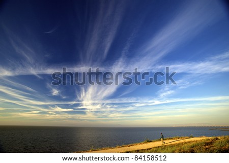 one person walking on a trail water and clouds in the background - stock photo