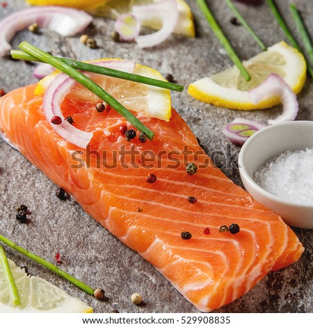One piece of fresh salmon with lemon pepper and salt.  stone background