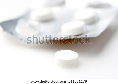One pill pressed out of the blister in the background