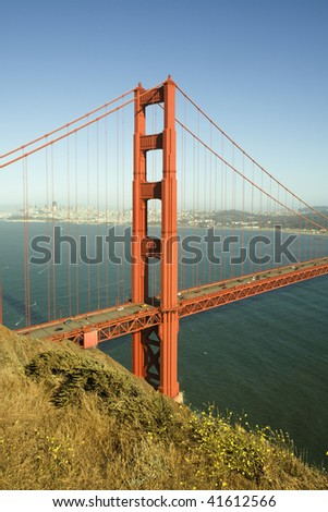 One pillar of Golden Gate bridge with suspension cables, green ocean and blue sky with clouds