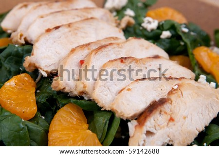 one plate of mandarin orange chicken salad with feta cheese over a bed of spinach - stock photo