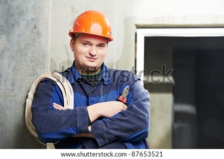 One Portrait of young Electrician in uniform with wire cable and pliers - stock photo