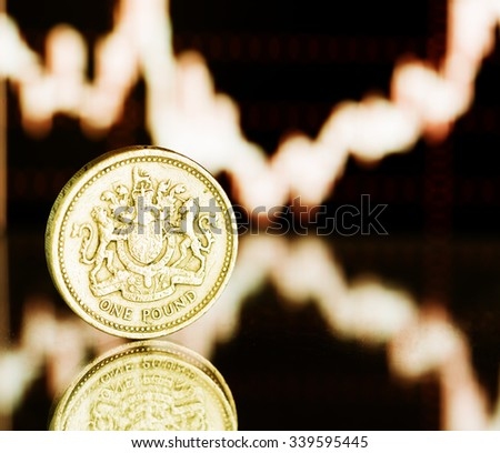 One pound coin. Fluctuating graph on black background (shallow DOF)  - stock photo