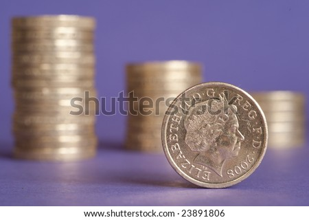 One pound coin in front of stacks of several coins against purple background - stock photo