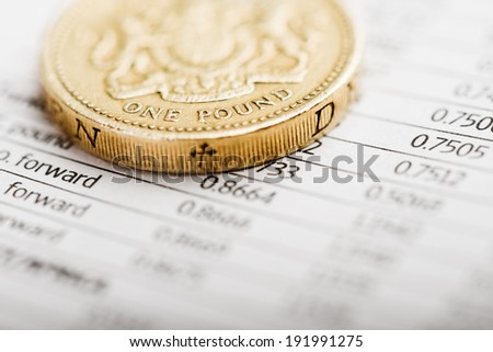 One pound coin on a summary table (shallow DOF)  - stock photo