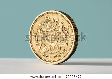 One pound coin stood up on blue background with copy space - stock photo