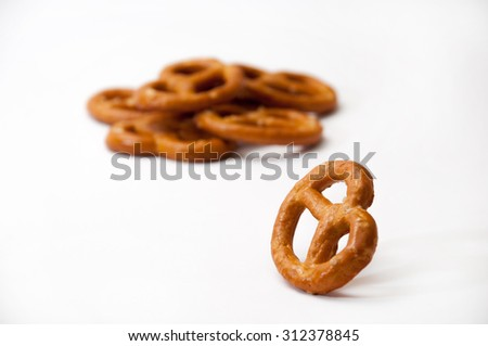 One pretzel and few pretzels in a pile on a white background. - stock photo