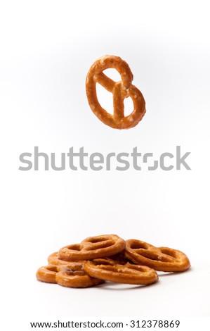 One pretzel flying and few pretzels on a white background. - stock photo