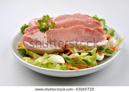 one raw organic pork chop and salad