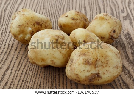 One raw potato lying on the wooden background. - stock photo