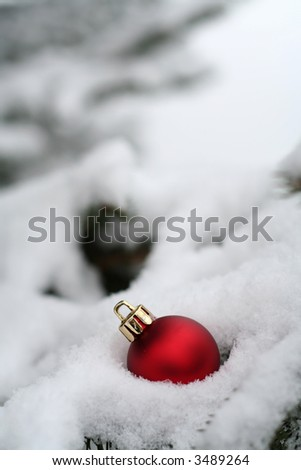 One red Christmas ornament on a pine tree in the snow - stock photo