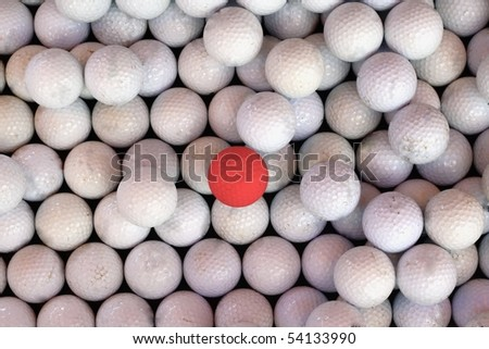 One Red Golf Ball Amongst a Sea of White Golf Balls. - stock photo