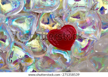 one red heart in a whole sea of translucent clear glass ones. Symbol of one true love, or being different and standing out - stock photo