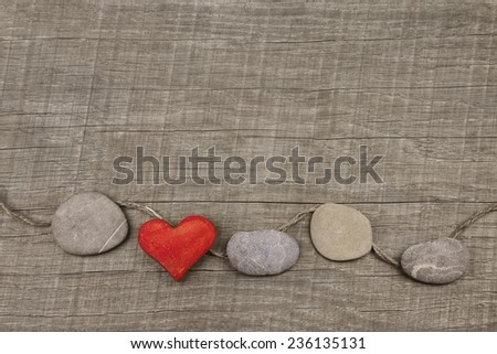 One red heart with stones on wooden background. Greeting card for lovers, friendship or valentine's day. - stock photo